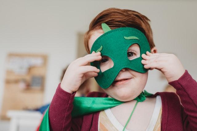 Litet barn med en grön mask