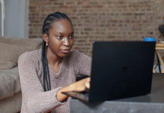 kvinna skriver CV på dator och ska söka jobb